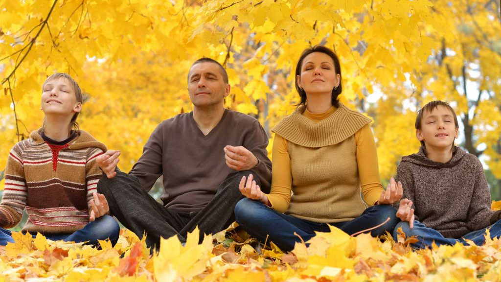 Mindfulness - Who Can Practice: image of a young family meditating in an autumn forest
